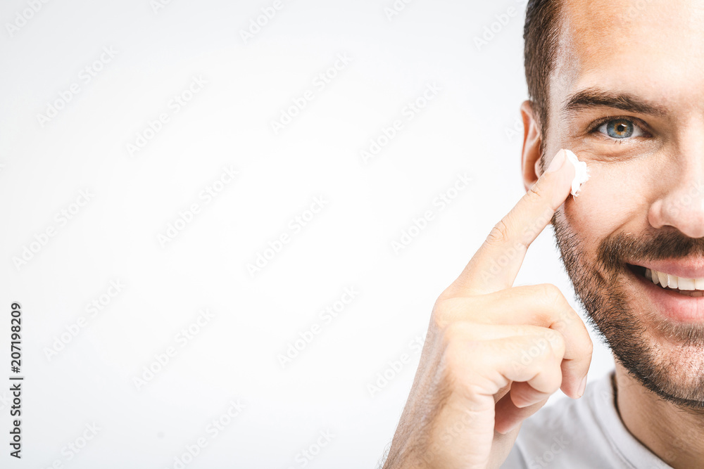 Fototapeta Skin care. Handsome young shirtless man applying cream at his face and looking at himself with smile while standing over gray background and looking at camera. Close-Up. Space for text.