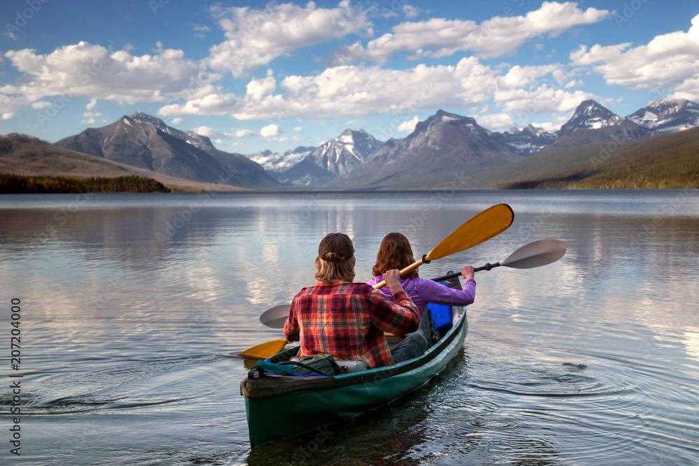 Valokuva  Adventurous traveling couple rowing a boat on a perfect scenic lake in a beautif
