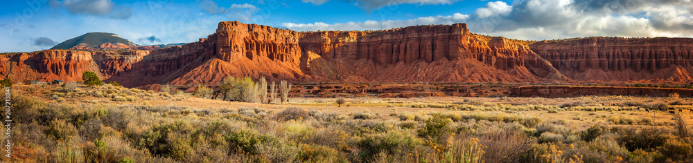 Fototapeta American Southwest Desert Landscape. Classic eroded Navaho sandstone bluffs and blue skies bring up an image of the old west. This is especially true here in Torrey, Utah, near Capitol Reef Park.