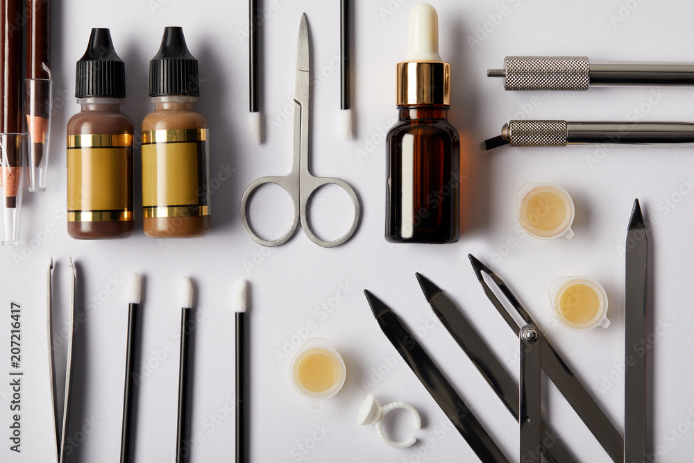 Fototapety, obrazy: top view of various tools and cosmetics for permanent makeup on white
