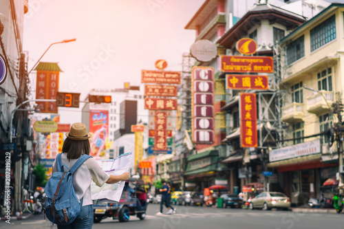 Young asian woman traveler with blue backpack and hipster hat looking map on road with tuk tuk Thailand background at China Town Bangkok Wallpaper Mural