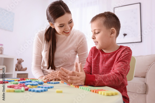 Fototapeta Young nanny playing with cute little boy at home obraz