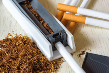 A Pile Of Natural Tobacco On A White Wooden Table And A Device For Manual Cigarette Making. Smoking. Nicotine Addiction. Health Hazard.