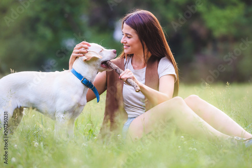 Obraz Beautiful young girl playing with a puppy Labrador Retriever in the park  - fototapety do salonu