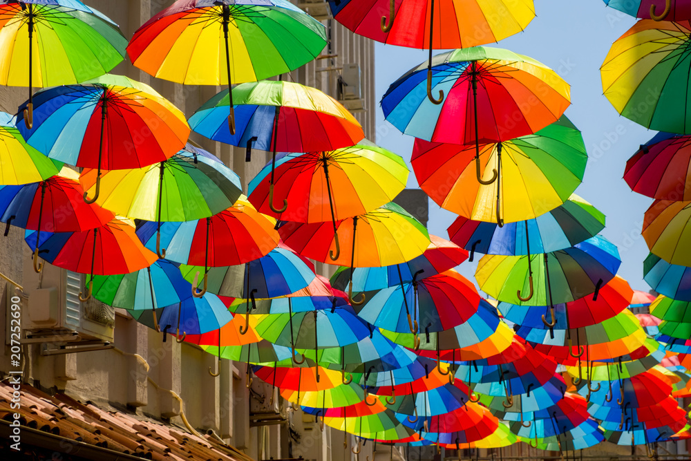 Fototapety, obrazy: Multicolored, rainbow, umbrellas hung over the street.