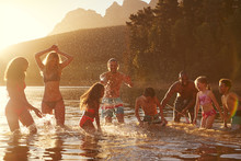 Family With Friends Enjoying Evening Swim In Countryside Lake