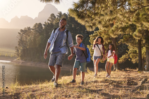 Children Walk By Lake With Parents On Family Hiking Adventure