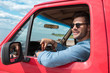 handsome smiling man in sunglasses driving car during road trip