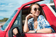 smiling young woman in sunglasses in car during trip