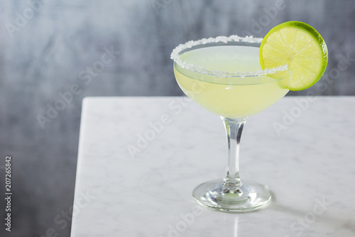 Fotografie, Obraz  Chilled Margarita Served Straight Up in a Goblet with Salted Rim on Marble Bar
