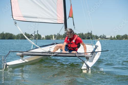 Poster Zeilen man leaning across catamaran