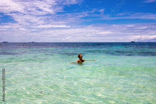 woman enjoy her bath in the beautiful water of exotic island, raja ampat archipe Poster