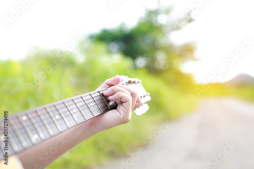 Valokuva Close-up male hand playing on acoustic guitar outdoor with rays of sunlight
