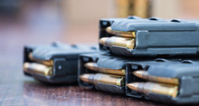 Magazines With Bullets Of Firearm Putted On Wooden Table. Close Up View, Blurred Background.