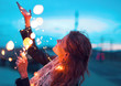 Happy woman playing with fairy light garland at evening