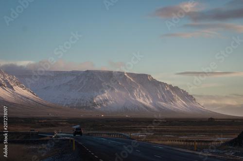 Staande foto Zwart Landscape with a car on a long road in Iceland in winter