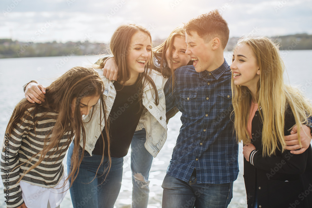 Fototapeta Summer holidays and teenage concept - group of smiling teenagers with skateboard hanging out outside.