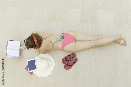 Papiers peints Magasin de musique Attractive young woman in swimsuit and sunglasses lying and listening music on headphones