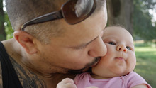 CLOSE UP Cheerful Muscular Dad Kisses His Adorable Newborn Daughter On The Cheek
