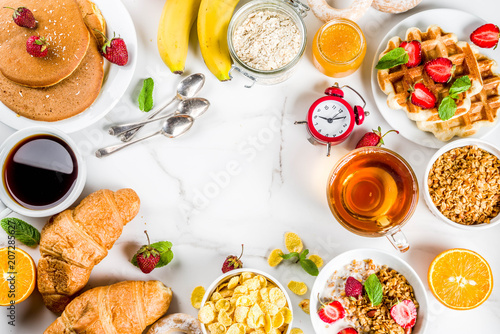 Fototapeta Healthy breakfast eating concept, various morning food - pancakes, waffles, croissant oatmeal sandwich and granola with yogurt, fruit, berries, coffee, tea, orange juice, white background obraz