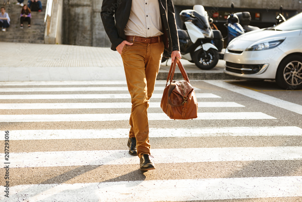 Fototapety, obrazy: Cropped photo of stylish successful man in business wear walking through pedestrian crossing in downtown, with leather male bag in hand