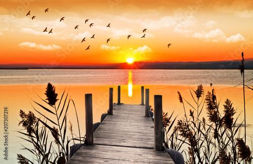 atardecer sobre el embarcadero de madera del lago