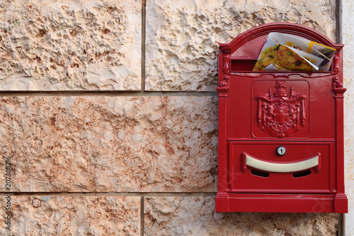 Fotografía red mailbox with advertising on tiled wall with pink marble