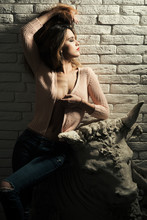 Girl In Undressing Near Artwork. Taurus Zodiac Sign Concept. Lady Sexy And Attractive Lean On Clay Sculpture Of Bull Or Taurus. Girl With Makeup On Calm Mysterious Face, White Brick Wall Background