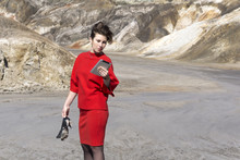 Woman In A Red Business Suit Is Standing In A Deserted Canyon With Shoes In Her Hand, Looking At The Tablet..