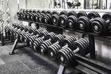 Rows of metal heavy dumbbells on rack in the sport gym, monochrome color tone. Sports equipment for weight training.