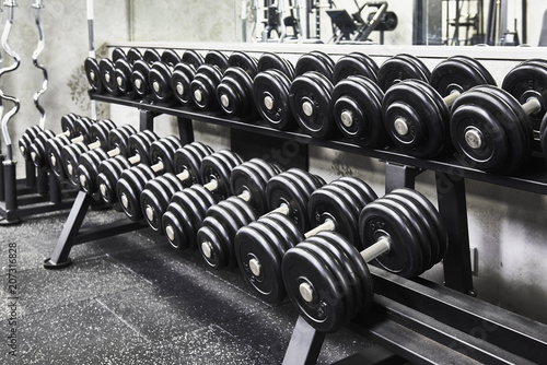 Fototapeta Rows of metal heavy dumbbells on rack in the sport gym, monochrome color tone. Sports equipment for weight training. obraz