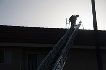 Los-Angeles, California, USA, 19.06.2014-a Fire On The Third Street/s.normandie 247  And The Work Of The Fire Department Of Los Angeles - Fireman Climbed The Stairs To The Roof Contour Photo.