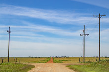 The Road Less Traveled - A Rural Cross Roads With A Red Dirt Road Leading Forward Over The Horizon In Farm Country Under Very Blue Sky