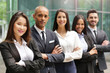 Portrait of business people of different ethnic backgrounds dressed in suits, they smile and cross their arms. Concept of: internationality and career, cooperation and team.