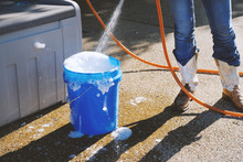 Summer Lifestyle Scene With Woman In Cowboy Boots Filling Blue Bucket Of Soapy Water To Do Cleaning Chores.