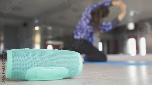 Obraz Wireless speaker in front of young woman stretching on the rug - fototapety do salonu