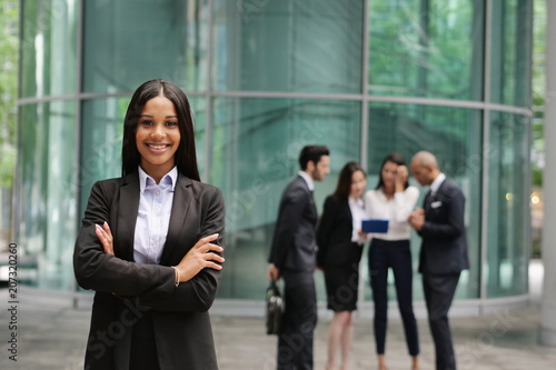 фотографія Portrait of a business woman, in a suit, happy and smiling and in the background a group of multi-ethnic business people