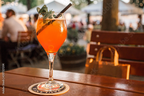 Aperol Spritz Cocktail. Alcoholic orange beverage on the table at the sunset lights. Bremen, Germany.