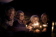 Four Senior Adult People Celebrate With Sparkle Fire Light At The Night For New Year Eve Or Just For A Dinner At Holiday. Retired Lifestyle Enjoy Leisure And Stay Together Having Fun And Party