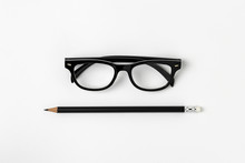 Glasses And A Black Pencil On White Background