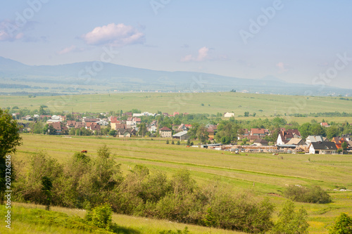 Fotobehang Blauwe hemel A beautiful landscape of Polish mountains. Green grass, a few houses and Tatra mountains in the background