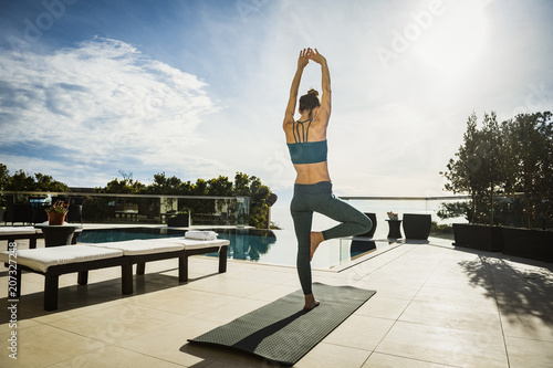Woman practicing yoga by swimming pool