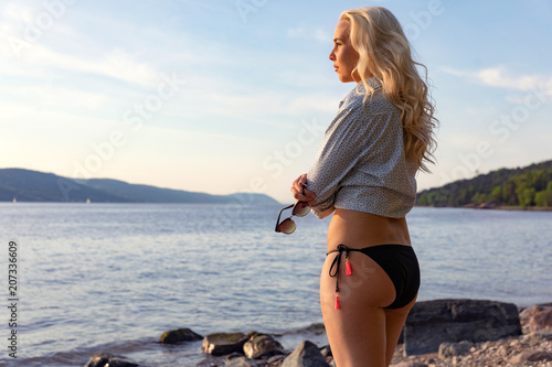 Pensive young woman standing alone at the beach in summer Canvas-taulu