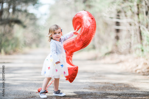 Blonde white female toddler wearing a grey and white dress with multi colored butterflies pointing at a red number two balloon smiling at camera Poster