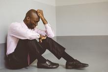 Upset Businessman Sitting On Floor