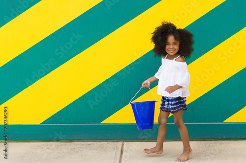 Portrait of smiling girl walking against wall