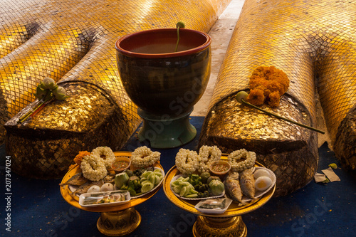 Photo  Giant standing golden Buddha close up of the toes and offerings at Beautiful Wat