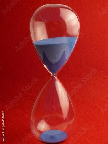 Fotografie, Obraz  hourglass framed in the center running blue sand under red felt paper background