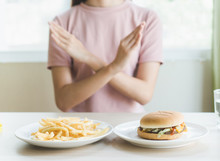 Woman On Dieting For Good Health Concept. Woman Doing Cross Arms Sign To Refuse Junk Food Or Fast Food (hamburger And Potato Fried) That Have Many Fat.