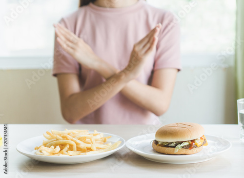 Fototapeta Woman on dieting for good health concept. Woman doing cross arms sign to refuse junk food or fast food (hamburger and potato fried) that have many fat. obraz